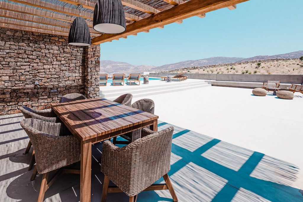 The villa Astrea, terrace with dining table & view. A luxury private pool villa in Ftelia, Mykonos.
