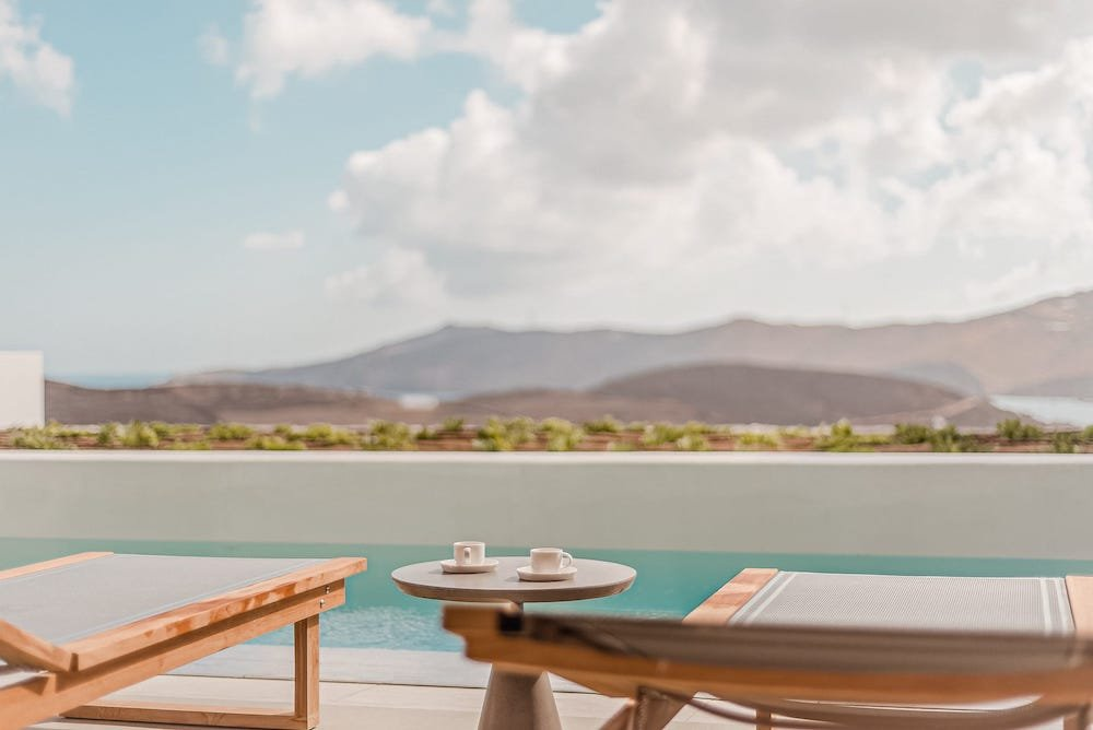 The villa Iris private terrace with table and sun beds. A 1 bedroom luxury villa in Ftelia, Mykonos.