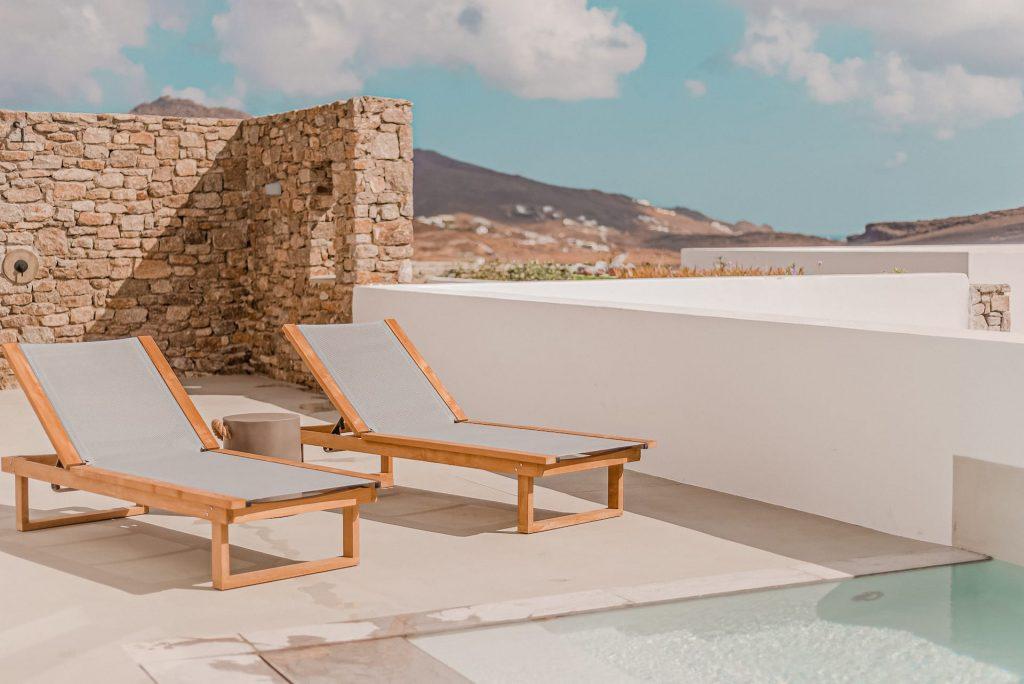 The villa Iris sun beds by the pool. A 1 bedroom luxury villa in Ftelia, Mykonos with modern design.